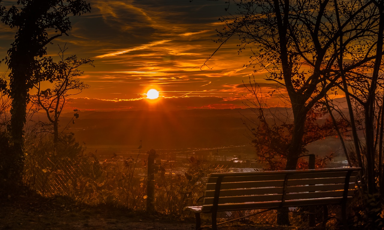 sunset over a town, bench in foreground