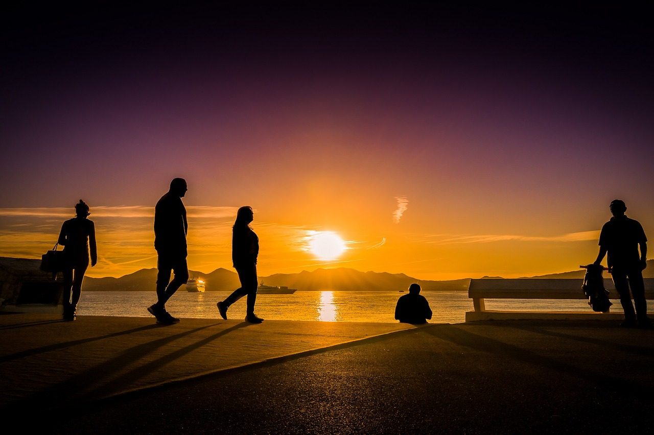 Walkers in silhouette against sunset